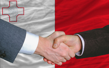 businessmen handshake after good deal in front of malta flag