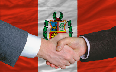 businessmen handshake after good deal in front of peru flag