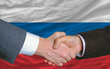 businessmen handshake after good deal in front of russia flag