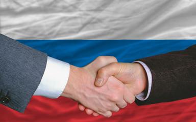 businessmen handshake after good deal in front of russia flag