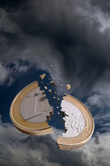 A one euro coin is broken in a stormy sky
