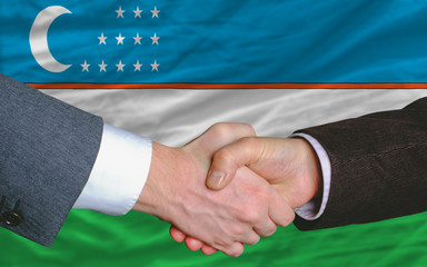 businessmen handshake after good deal in front of uzbekistan fla