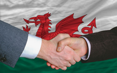 businessmen handshake after good deal in front of wales flag