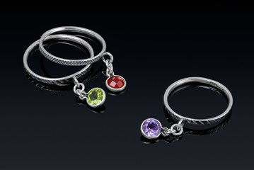 Silver ring with colored stones with reflection.