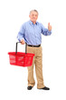 Senior man holding an empty shopping basket and giving thumb up