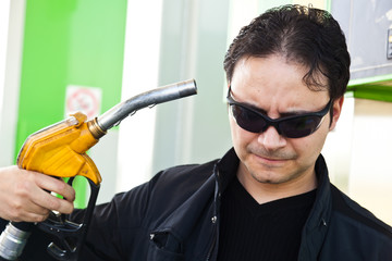 Man pointing a fuel pump nozzle at his head