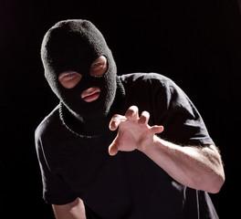 aggressive burglar in black mask
