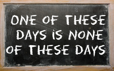 "Proverb ""One of these days is none of these days"" written on a b"