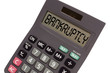 "Old calculator on white background showing text ""bankruptcy"" in"