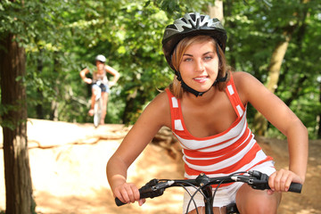 Teenage girls riding bikes through the forest