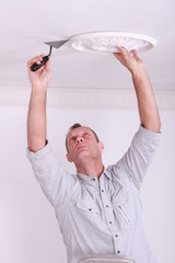 Man fitting a ceiling rose