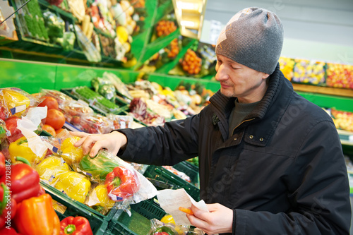 woman choosing vegetables in supermarket store