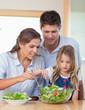 Portrait of a family preparing a salad