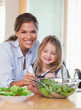 Portrait of a young mother and her daughter preparing a salad
