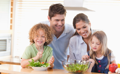 Happy family preparing a salad together