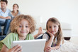 Happy children using a tablet computer while their happy parents