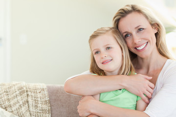 Mother embracing daughter on couch