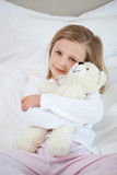 Girl embracing her teddy on the bed