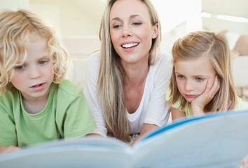 Mother reading magazine with her children