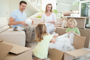 Family unpacking cardboard box in the living room