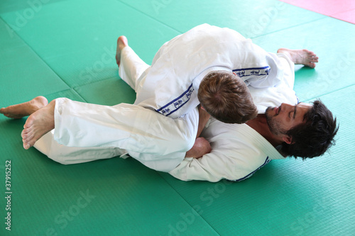 Judo practitioners in a hold on mat