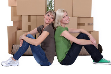 Two women stood by pile of boxes