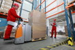 two workers working in storehouse with forklift loader