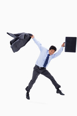 Businessman jumping while holding his jacket and a briefcase