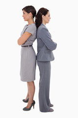 Businesswomen with arms folded standing back on back