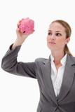 Bank employee taking close look at piggy bank