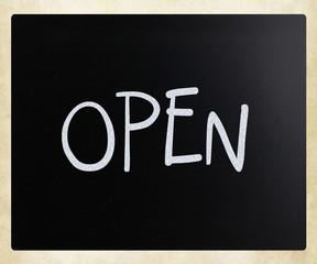 "The word ""Open"" handwritten with white chalk on a blackboard"