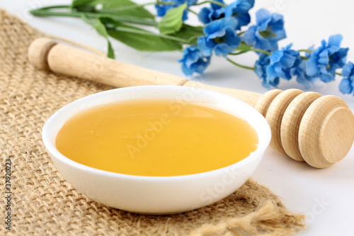 fresh golden honey in jar with a wooden spoon and flowers
