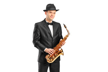 A man in a suit holding a saxophone