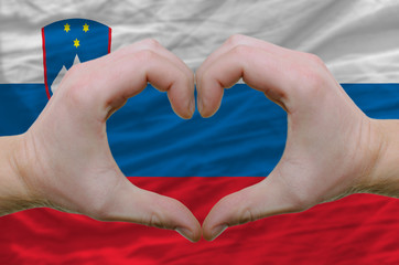 Heart and love gesture showed by hands over flag of slovenia bac