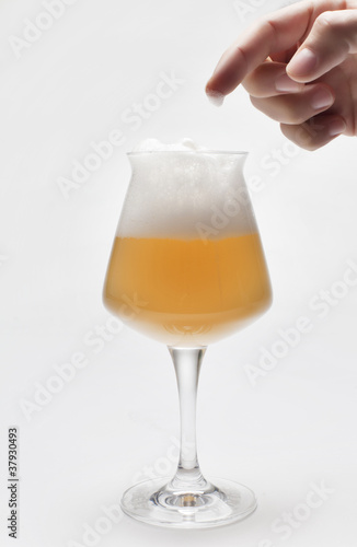 birra con schiuma e mano