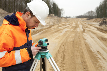 Road construction, land surveyor looking at equipment