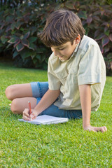 boy writing in note book on green lawn