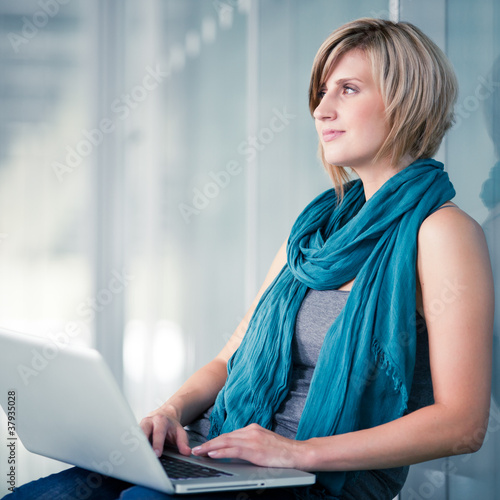 Pretty young female student with a laptop computer on college