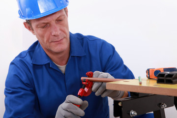 Mature plumber using a pipe cutter
