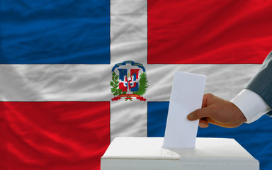 man voting on elections in dominican republic in front of flag