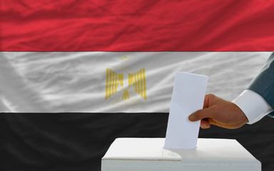 man voting on elections in egypt in front of flag