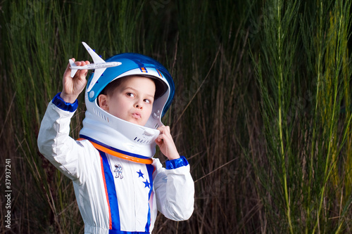 Young boy playing with a toy airplane.