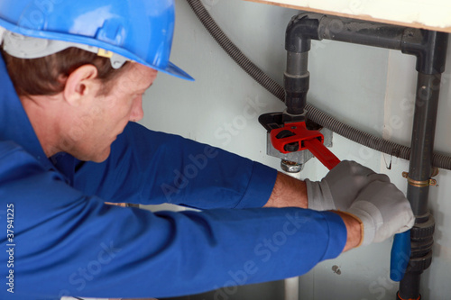Man using a large red wrench on some interior water pipes