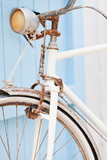 Old bicycle leaning against blue door. Shallow deep of focus.