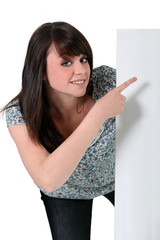 Teenage girl pointing to a white sign