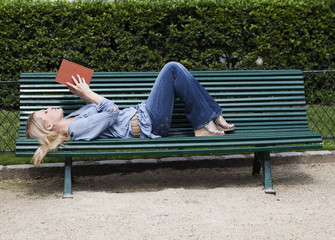 young woman reading a book on a bench