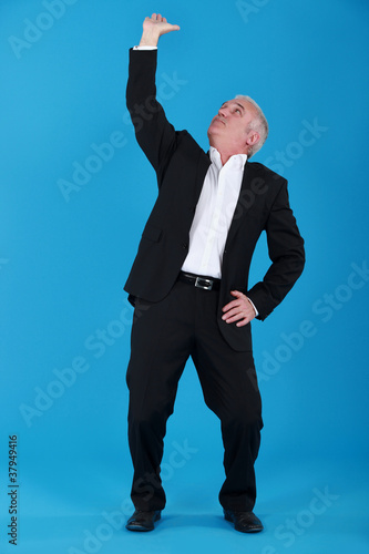 Businessman pushing ceiling