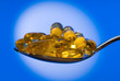 Omega 3 fish oil capsules on a spoon.