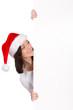 junge frau mit weihnachtsmütze hält werbeschild