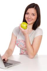 teenager isst einen apfel am computer